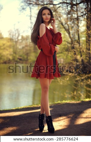 Full length portrait of young beautiful pretty girl posing outdoors near water in park. Stylish woman walking in summer park - stock photo