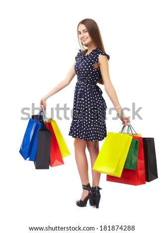 Full length portrait of young beautiful smiling happy woman holding many colorful shopping bags,turning around, isolated on white background