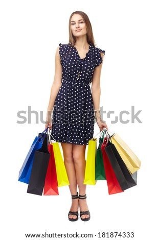 Full length portrait of young beautiful smiling woman holding many colorful shopping bags isolated on white background