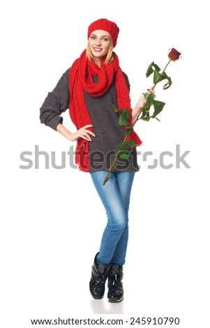 Full length portrait of young beautiful woman holding red rose, over white background
