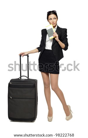 Full length portrait of young business woman standing with her travel bag, holding the tickets with passport, looking sideways at blank copy space, isolated on white background - stock photo