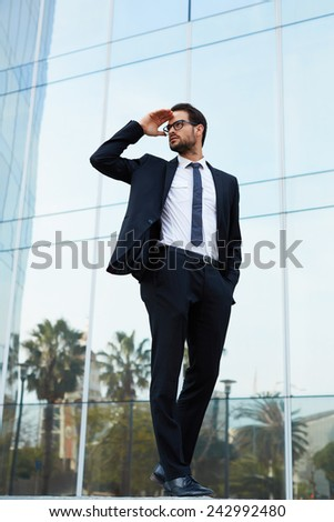 Full length portrait of young businessman looking off in the distance holding up his hand - stock photo