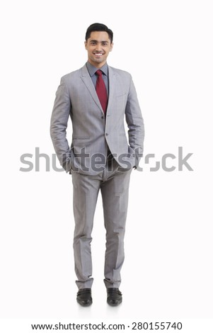 Full length portrait of young businessman with hands in pockets isolated over white background - stock photo