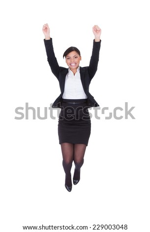Full length portrait of young businesswoman jumping with arms raised over white background - stock photo
