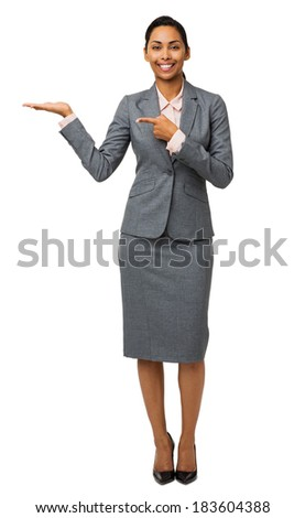 Full length portrait of young businesswoman pointing at invisible product against white background. Vertical shot. - stock photo
