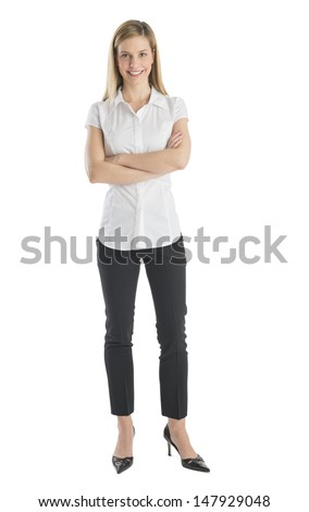 Full length portrait of young businesswoman smiling while standing arms crossed isolated on white background - stock photo