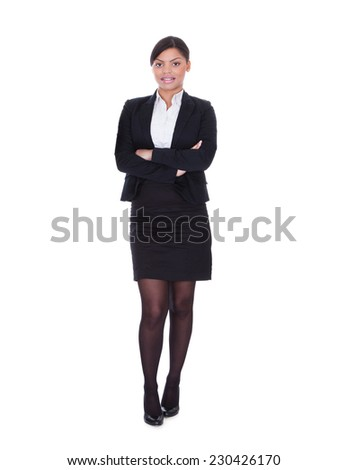 Full length portrait of young businesswoman standing arms crossed over white background - stock photo