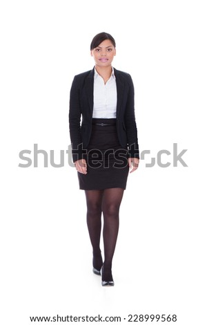 Full length portrait of young businesswoman walking over white background - stock photo