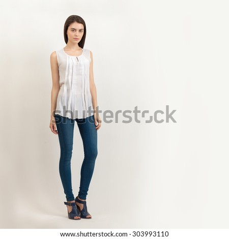 Full length portrait of young calm beautiful brunette woman posing for model tests against white background - stock photo