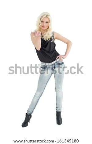 Full length portrait of young casual woman with blonde hair over white background - stock photo