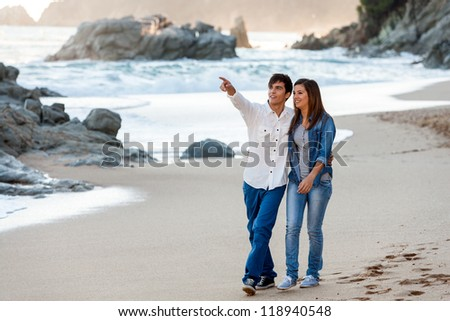 Full length portrait of young couple sitting on rocks at seaside. - stock photo