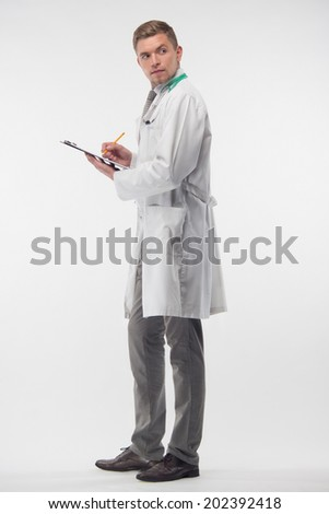 Full length portrait of young doctor in the white coat and with stethoscope, writing names of new patients in his notebook and looking back. Isolated on the white background
