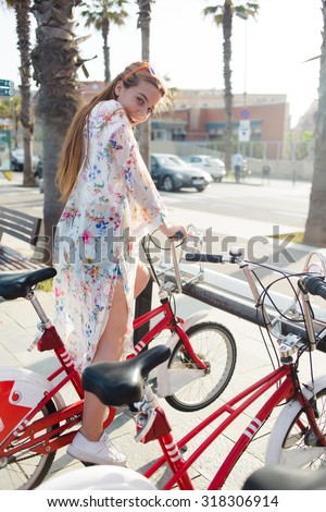 Full length portrait of young fashionable woman with charming smile sitting on bike for excursions having fun during holidays, happy female with trendy look posing with vintage bicycle in summer day - stock photo