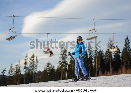 Full length portrait of young female skier against ski-lift and forest on a sunny day. Woman is wearing helmet skiing glasses gloves and blue ski suit. Ski resort at Carpathian Mountains, Bukovel - stock photo