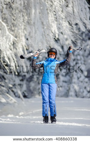 Full length portrait of young happy female skier standing enjoying sunny day against beautiful snow covered trees on the background. Girl is holding her skis and ski poles up. Bukovel, Ukraine - stock photo