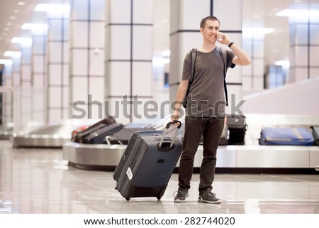 Full length portrait of young happy smiling handsome traveller man in 20s leaving arrivals lounge of airport terminal building after collecting his baggage at conveyor belt, talking on cellphone - stock photo