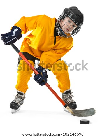 Full length portrait of young hockey player in yellow uniform, with stick and puck. On the white background - stock photo