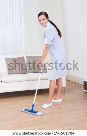 Full length portrait of young maid cleaning floor with mop at home