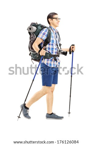 Full length portrait of young male tourist walking with hiking poles isolated on white background - stock photo