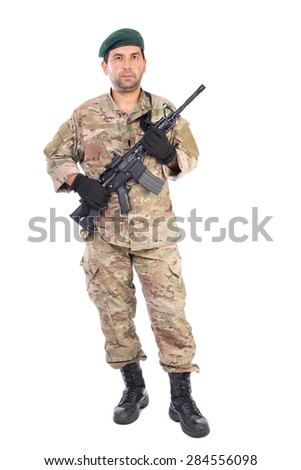 Full length portrait of young man in army clothes holding a weapon against white background - stock photo
