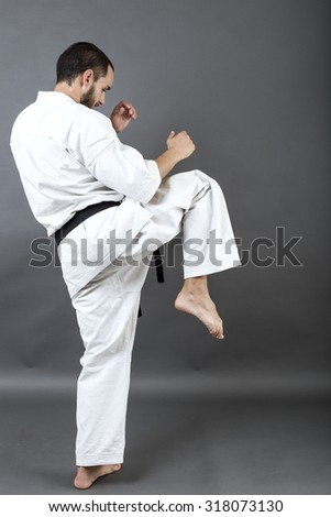 Full length portrait of young man in white kimono and black belt training martial art over gray background - stock photo