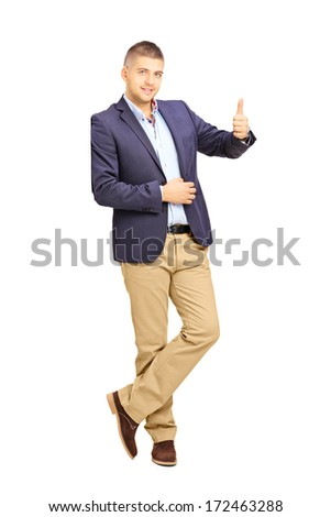 Full length portrait of young man leaning against a wall and giving a thumb up isolated on white background