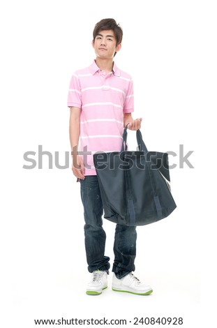Full length portrait of young man standing and holding a bag. - stock photo