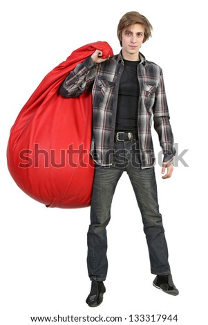 Full length portrait of young man standing with big bean bag on white background - stock photo