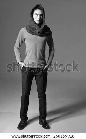 Full length portrait of young man standing with hands in pockets - stock photo