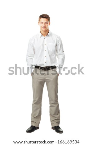 Full length portrait of young man wearing white shirt and light trousers with hands in pockets isolated on white background - stock photo