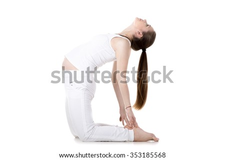 Full length portrait of young pregnant fitness model in sportswear doing yoga or pilates training, warming up, bending in Ustrasana, Camel Pose, white background, studio, isolated