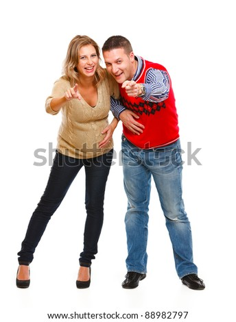Full length portrait of young pregnant woman with husband pointing in camera on white background - stock photo