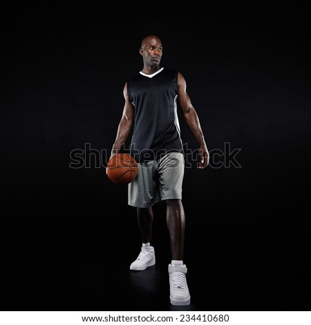 Full length portrait of young professional basketball player standing over black background. African young man in sportswear with basketball. - stock photo