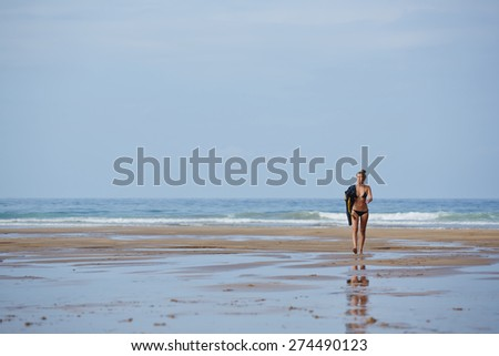 Full length portrait of young sexy woman in bikini walking down wet sand reflecting blue sky light at sunny day, seductive woman in swimsuit walking on the beach wit copy space sky