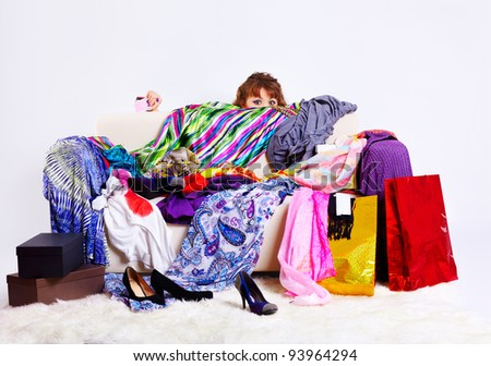 full-length portrait of young shopaholic woman with credit cards hiding behind sofa with a lot of clothes and shopping bags - stock photo
