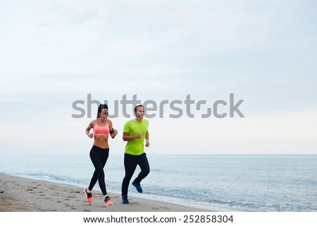 Full length portrait of young smiling couple running along the beach, athletic attractive people jogging in active wear enjoying perfect evening outdoors - stock photo