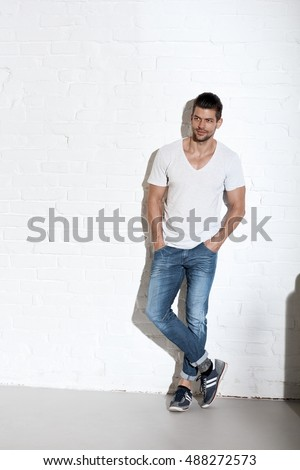 Full-length portrait of young sporty caucasian man in casual clothing, looking away. Copyspace.