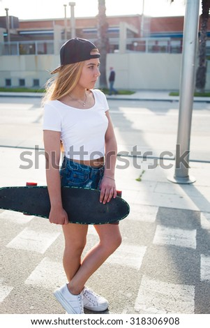 Full length portrait of young stylish hipster girl holding long board with copy space for your brand, attractive trendy woman skateboarder standing with penny board on the street in sunny summer day - stock photo