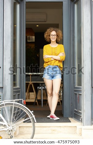 Full length portrait of young successful businesswoman standing in her small coffee shop entrance.