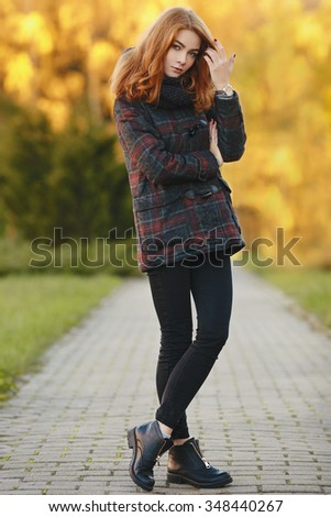Full length portrait of young trendy redhead woman  in scarf and plaid jacket with autumn foliage background outdoors