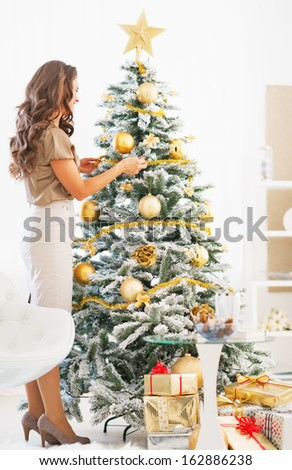 Full length portrait of young woman decorating christmas tree with christmas ball - stock photo