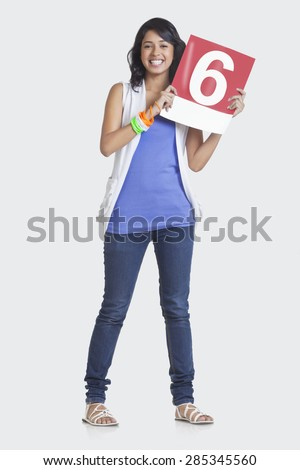 Full length portrait of young woman in casuals signaling a six over white background - stock photo