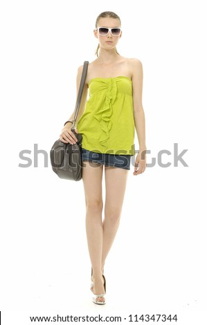full length Portrait of young woman in short jeans holding handbag walking