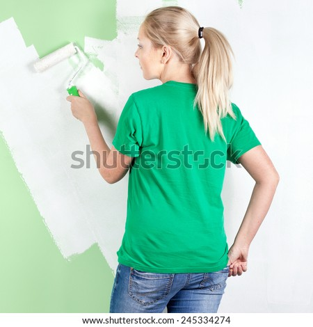 Full length portrait of  young woman painting the wall