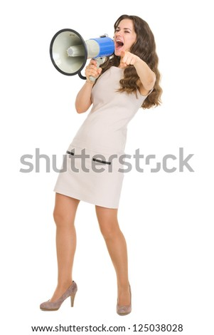 Full length portrait of young woman shouting in megaphone and pointing in camera
