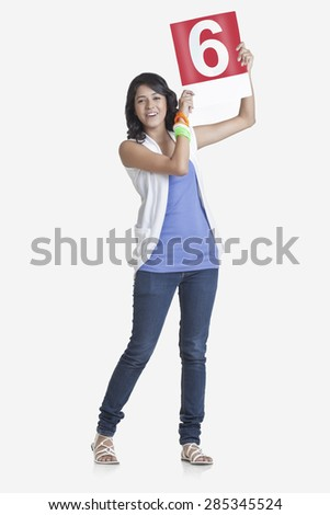 Full length portrait of young woman signaling a six over white background - stock photo