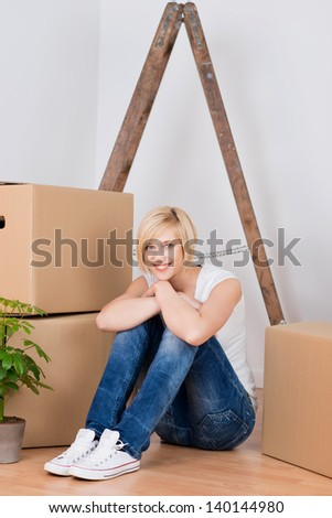 Full length portrait of young woman with cardboard boxes sitting on hardwood floor - stock photo