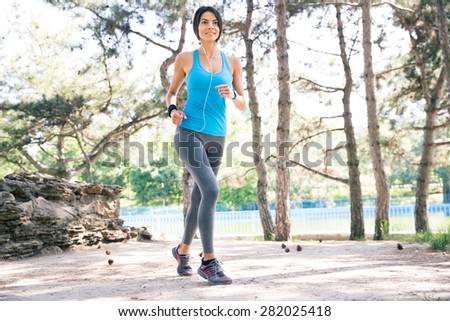 Full length portrait pf a happy fitness woman running outdoors in park - stock photo