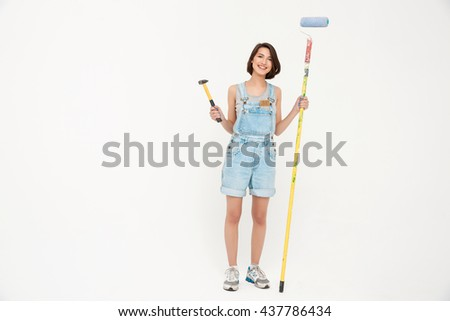 Full length portrait pretty girl, in gray shirt and denim overall, holding hammer and painting roller, isolated on white background - stock photo