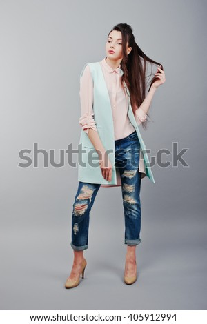 Full-length portrait young brunette girl wearing in pink blouse, turquoise jacket, ripped jeans and cream shoes .Fashion studio shot - stock photo